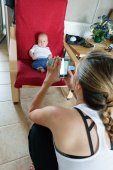 Mother taking photograph of her baby