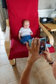 Mother photographing her baby boy sitting on armchair using mobile camera