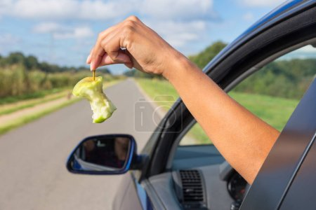 Female arm dropping apple core out car window