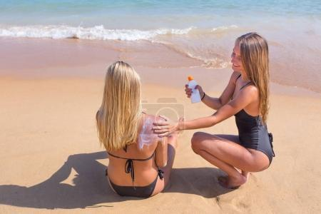 Photo for Young dutch woman rubs sunscreen on skin of girlfriend - Royalty Free Image