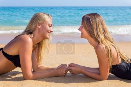 Photo for Two young caucasian women lying opposite on beach - Royalty Free Image