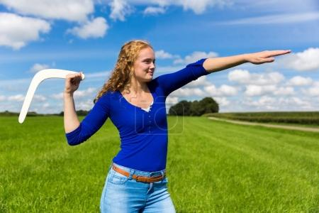 Photo for Young caucasian woman throwing boomerang in nature - Royalty Free Image