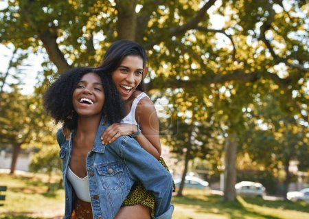Photo for Two female best friends having fun in the park laughing and giving piggy backs - Royalty Free Image