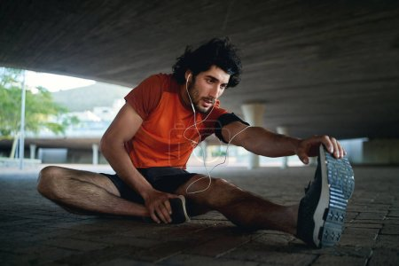 Young man athlete with earphone in his ears warming up and stretching his legs before running in the city street under the bridge