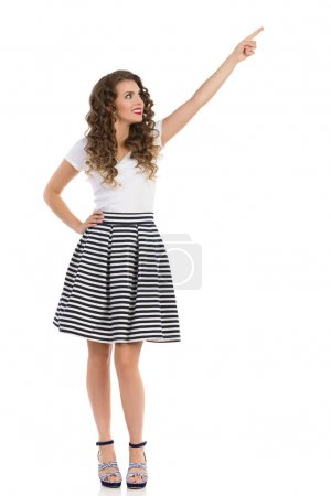 Photo pour Belle jeune femme en mini jupe rayée, dessus blanc et talons hauts regardant vers le haut, pointant vers le haut. studio plein temps tourné isolé sur blanc. - image libre de droit