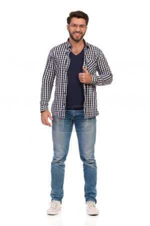 Photo for Handsome man in jeans, sneakers, glasses and unbuttoned lumberjack shirt is standing and looking at camera. Full length studio shot isolated on white. - Royalty Free Image