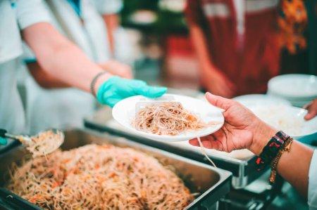 Photo pour Les pauvres reçoivent des dons de nourriture des donateurs : les mains des pauvres reçoivent de la nourriture des mains de l'humanité. - image libre de droit