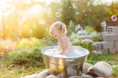 Photo for Happy toddler blonde girl with two ponytales playing with bubbles in a can pelvis outside at hot summer evening. Tempering and fun. Copyspace. - Royalty Free Image
