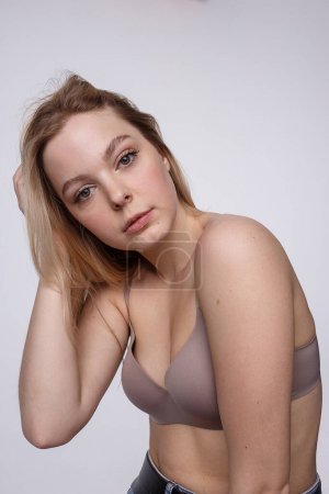 Photo pour Portrait de beauté d'une femme caucasienne aux longs cheveux blonds posant en lingerie beige sur fond blanc de studio. tests de modèle de jeune fille en bra. Femelle attrayante à peau propre - image libre de droit