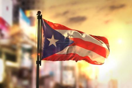 Puerto Rico Flag Against City Blurred Background At Sunrise Back