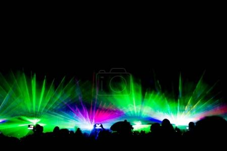 Colorful laser show nightlife club stage with smartphone filming