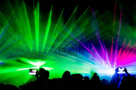 Colorful laser show nightlife club stage with smartphone selfies