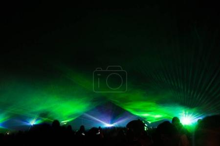 Colorful laser show nightlife club stage with party people crowd