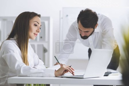 Man writing and woman working at laptop