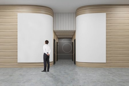 Photo for Rear view of a businessman in a white shirt looking at a poster in an office hall with rounded wooden walls. Rows of doors are leading to an elevator. 3d rendering. Mock up. - Royalty Free Image