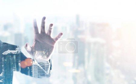 Businessman s hand, foggy city