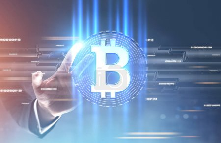 Photo for Hand of a businessman in a suit reaching for a shining bitcoin sign inside of a round badge. A futuristic background, a blurred abstract interface. Toned image double exposure mock up - Royalty Free Image