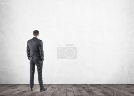 Photo for Portrait of a young businessman wearing a dark suit and standing with his hands in pockets. An empty room background, mock up - Royalty Free Image