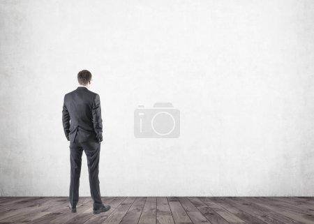 Photo pour Portrait d'un jeune homme d'affaires vêtu d'un costume sombre et debout les mains dans les poches. Un fond de pièce vide, maquette - image libre de droit