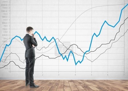 Side view of a thoughtful businessman, graphs