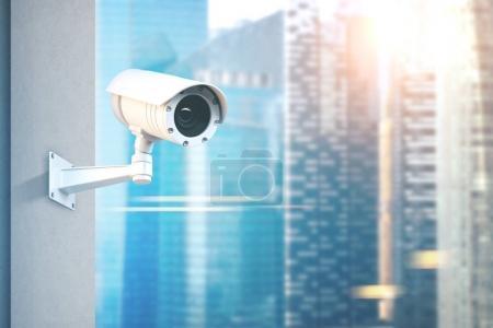 Photo pour Caméra de Cctv moderne sur un mur. Un floue gratte-ciel sur fond de journée ensoleillée Toned image double exposition simulée vers le haut - image libre de droit