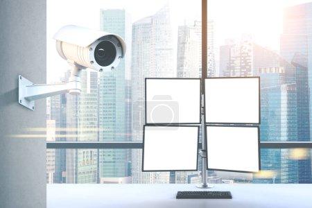 CCTV camera and four computer screens