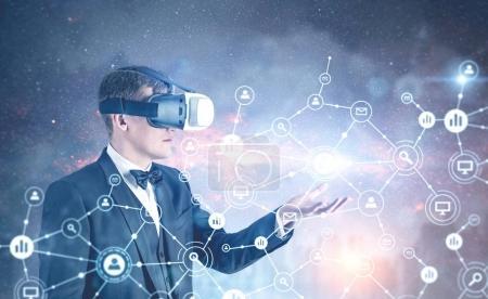 Businessman in VR glasses, network hologram