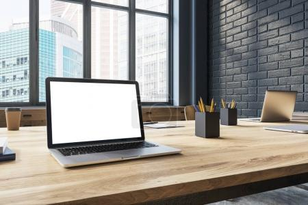 Photo for Laptop with a white screen is standing on a wooden table in an office with large windows and black brick walls. 3d rendering mock up - Royalty Free Image