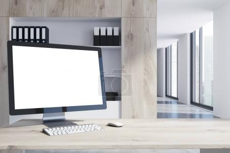 White computer screen on a wooden table