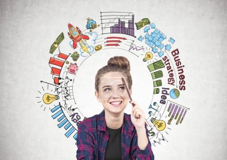 Photo for Smiling teen girl in a checkered shirt is sitting with a pencil near her forehead and thinking. She is looking up. A colorful round business plan sketch on a concrete wall. - Royalty Free Image