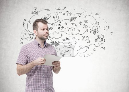 Photo for Bearded young man wearing a checkered shirt holding a blank paper and looking away. A concrete wall background with arrows sketch. - Royalty Free Image