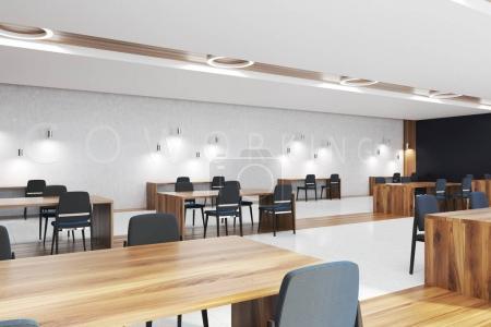 Foto de Rincón de coworking con paredes blancas, suelo de hormigón y madera, mesas de madera con sillas negras. maqueta de representación 3d - Imagen libre de derechos