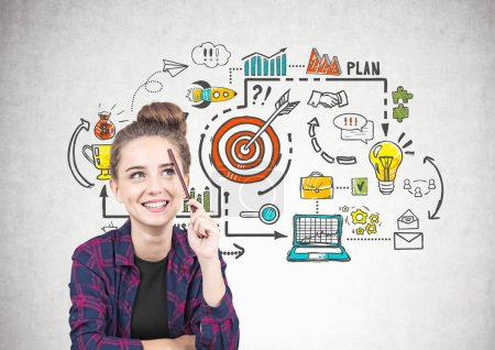 Photo for Smiling teen girl in a checkered shirt is sitting with a pencil near her forehead and thinking. She is looking up. A colorful business goals sketch on a concrete wall. - Royalty Free Image