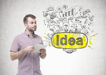 Bearded young man holding paper, business idea