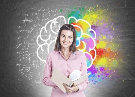 Photo pour Portrait d'une jeune femme souriante portant une chemise rose et tenant un cahier ouvert. Un fond de tableau noir avec une esquisse de cerveau coloré avec formule autour d'elle. - image libre de droit