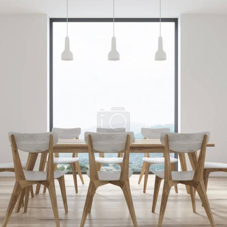 White dining table with design chairs, window
