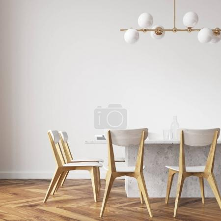 White dining table with design chairs close up