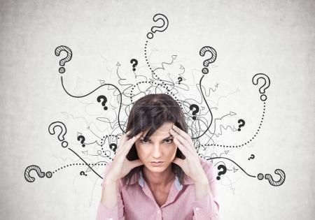 Photo for Stressed young woman wearing a pink shirt and sitting with her fingers touching her temples. A headache. A concrete wall with question marks - Royalty Free Image