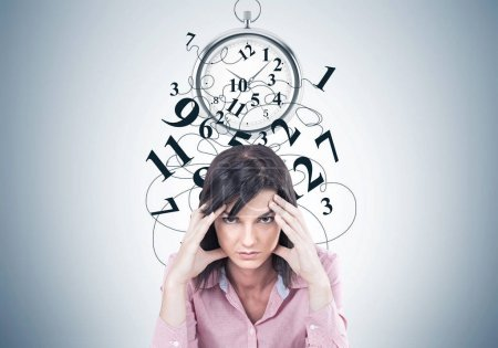 Photo for Stressed young woman wearing a pink shirt and sitting with her fingers touching her temples. A headache. A gray wall background with time management drawings - Royalty Free Image