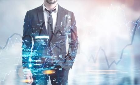 Photo for Unrecognizable young businessman wearing a suit with a tie and standing with a hand in a pocket. A night cityscape background with a graph. Toned image double exposure mock up - Royalty Free Image