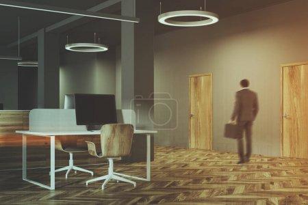 Dark and wooden office interior, man