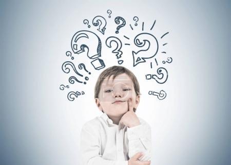 Thinking little boy, finger cheek question marks