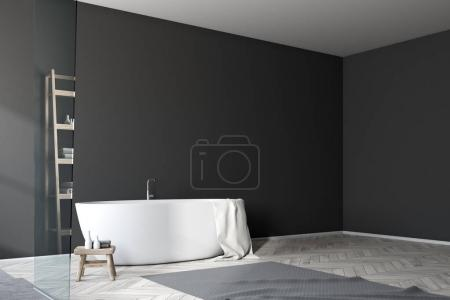 White bathtub in a black bathroom, side view
