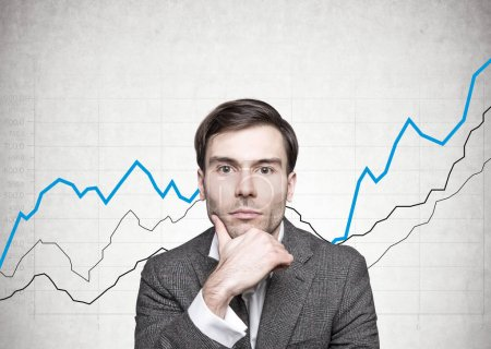 Thoughtful dark haired businessman, graphs