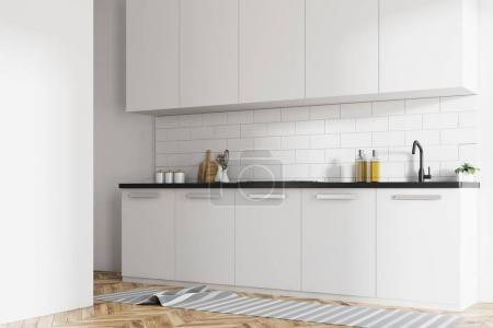 Photo for Modern kitchen interior with white brick walls, white countertops and a wooden floor with a rag on it. A side view. 3d rendering mock up - Royalty Free Image