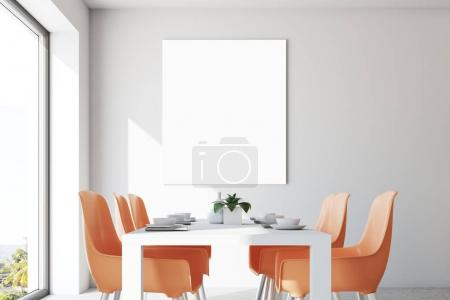 White dining room, orange chairs, poster close up