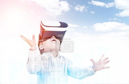Cute little boy in VR glasses, cloudy sky