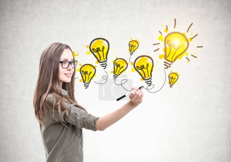 Photo for Smiling young woman wearing a khaki shirt and glasses and holding a marker. Yellow light bulbs on a concrete wall. An idea concept - Royalty Free Image