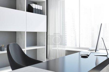 Photo pour Coin d'un milieu de travail de bureau moderne avec une table d'ordinateur, un président noir et une fenêtre avec une grande ville derrière elle. rendu 3D maquette - image libre de droit