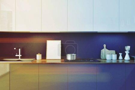 Photo pour Comptoirs de cuisine gris avec construit dans les appareils et une rangée de placards blancs suspendus au-dessus d'eux. Une affiche encadrée. maquettes 3D rendu image tonique - image libre de droit